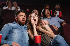 Shocked young couple watching a horror movie. At cinema stock photos