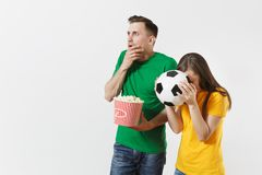 Shocked young couple, woman, man, football fans in yellow green t-shirt cheer up support team with soccer ball bucket of. European young couple, woman, man stock images