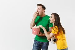 Shocked young couple, woman, man, football fans in yellow green t-shirt cheer up support team with soccer ball bucket of. European young couple, woman, man royalty free stock image