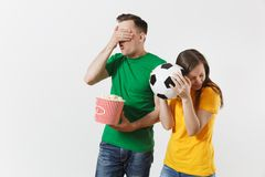 Shocked young couple, woman, man, football fans in yellow green t-shirt cheer up support team with soccer ball bucket of. European young couple, woman, man stock photography