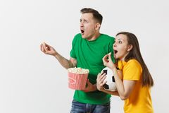 Shocked young couple, woman, man, football fans in yellow green t-shirt cheer up support team with soccer ball bucket of. European young couple, woman, man royalty free stock photo