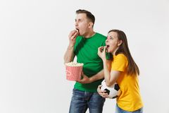 Shocked young couple, woman, man, football fans in yellow green t-shirt cheer up support team with soccer ball bucket of. European young couple, woman, man royalty free stock photos