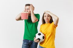 Shocked young couple, woman, man, football fans in yellow green t-shirt cheer up support team with soccer ball bucket of. European young couple, woman, man stock image