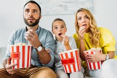 shocked young family watching movie at home with buckets