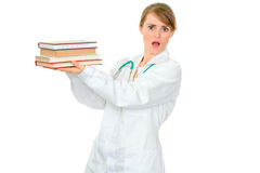 Shocked young female doctor holding medical books Stock Photos