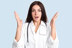 Shocked young female therapist clasps hands and looks surprisingly at camera, can`t believe in death of patient, has scared look,. Dressed in lab gown, gestures royalty free stock image