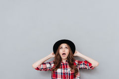 Shocked young girl in hat looking up at copyspace Stock Images