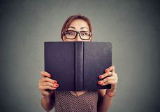 Shocked young girl hiding behind an open book. Close up portrait of a shocked young girl hiding behind an open book isolated on gray wall background Stock Photography