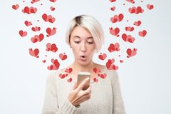 Shocked young girl looking at mobile phone screen in surprise reading sms. Declaration of love concept. A lot of heart signs. Flying next to her royalty free stock photos