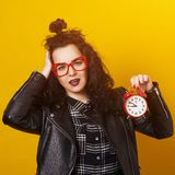 Shocked young hipster woman holding alarm clock, isolated on yellow background. Copy space. Woman in black leather jacket and glas royalty free stock image