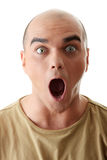 Shocked young man. Closeup portrait of a shocked young man looking straight on a white background Stock Photography