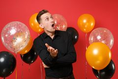 Shocked young man in black classic shirt looking up spreading hands on bright red background air balloons. Valentine`s