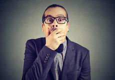 Shocked young man covering his mouth with hands royalty free stock image