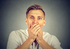 Shocked young man covering his mouth with hands Stock Photo