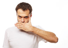 Shocked young man  covering mouth with hands Royalty Free Stock Images