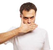 Shocked young man  covering mouth with hands Royalty Free Stock Photography