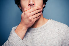 Shocked young man with his hand on his mouth Stock Image