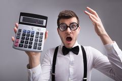 Shocked Young Man Holding Calculator stock image