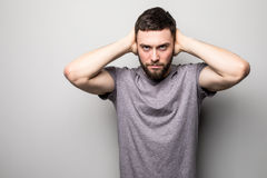 Shocked young man in plaid shirt holding over head with both hands over grey background Stock Images