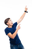 Shocked young man pointing finger up Stock Photo