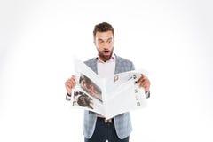 Shocked young man reading gazette. Royalty Free Stock Photo