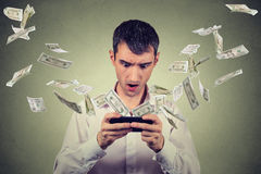 Shocked young man using smartphone with dollar bills banknotes flying away Stock Photos