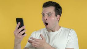 Shocked Young Man Using Smartphone Isolated on Yellow Background. The Shocked Young Man Using Smartphone Isolated on Yellow Background, high quality stock footage