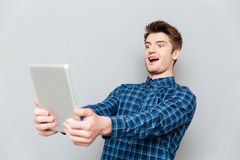 Shocked young man using tablet computer. Picture of shocked young man standing over grey wall and using tablet computer. Looking aside Stock Photo