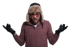 Shocked young man in winter clothes and fur hat Stock Photos