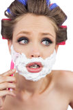 Shocked young model in hair curlers posing with razor Stock Image