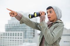 Shocked young model in winter clothes showing something in the sky. Outside on a cloudy day Stock Image