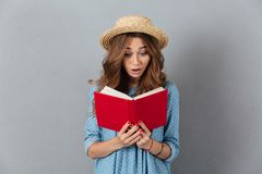 Shocked young pretty woman reading a book. Looking aside. Stock Images