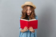 Shocked young pretty woman reading a book. Looking aside. Stock Photography