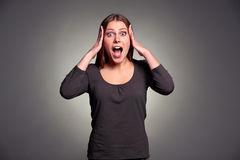 Shocked young woman. Studio shot of shocked young woman over dark background Stock Photography