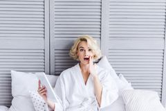 Shocked young woman in bathrobe holding digital tablet and looking at camera. In bedroom stock photography