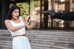 Shocked young woman being threatened by man thief with gun Stock Image