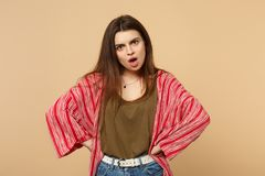 Shocked young woman in casual clothes swearing, standing with arms akimbo on waist isolated on pastel beige wall. Background in studio. People sincere emotions stock photography