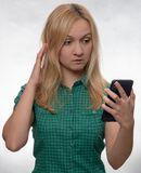Shocked young woman in casual green shirt with smartphone in hand looking at phone stock photo
