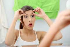 Shocked young woman checking her wrinkles. On her forehead at bathroom Stock Photo