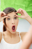 Shocked young woman checking her wrinkles. On her forehead at bathroom Royalty Free Stock Image