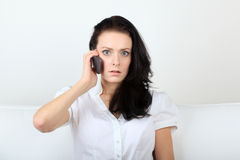 Shocked young woman communicates via her cell phone with eye contact.  royalty free stock photos