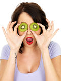 Shocked Young Woman Covering Eyes with Fresh Kiwi Fruit Royalty Free Stock Photography