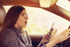 Shocked woman distracted by mobile phone texting while driving a car stock photography