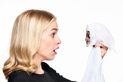 Shocked young woman face to face with Halloween skeleton death decoration. Halloween concept over white. stock images