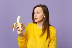Shocked young woman in fur sweater holding in hand, looking on fresh ripe banana fruit isolated on violet pastel wall royalty free stock photography
