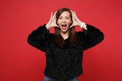 Shocked young woman in fur sweater keeping mouth wide open looking surprised, holding hands near face isolated on bright stock photos