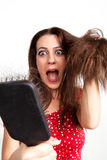 Shocked young woman with hair brush Royalty Free Stock Photography