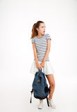 Shocked young woman holding backpack and looking away. Isolated on a white background Royalty Free Stock Image