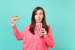 Shocked young woman in knitted pink sweater hold in hands eclair cake, plastic cup of cola or soda isolated on blue. Shocked young woman in knitted pink sweater royalty free stock image