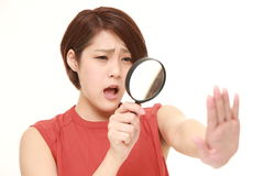 Shocked young woman looking through a magnifying glass her nails Royalty Free Stock Photos